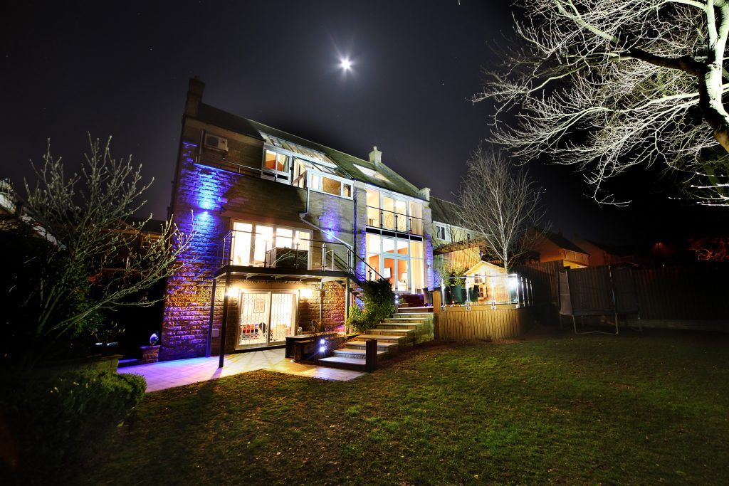 night photograph of a large 5 bedroom property showing it's fun lighting and different aspects